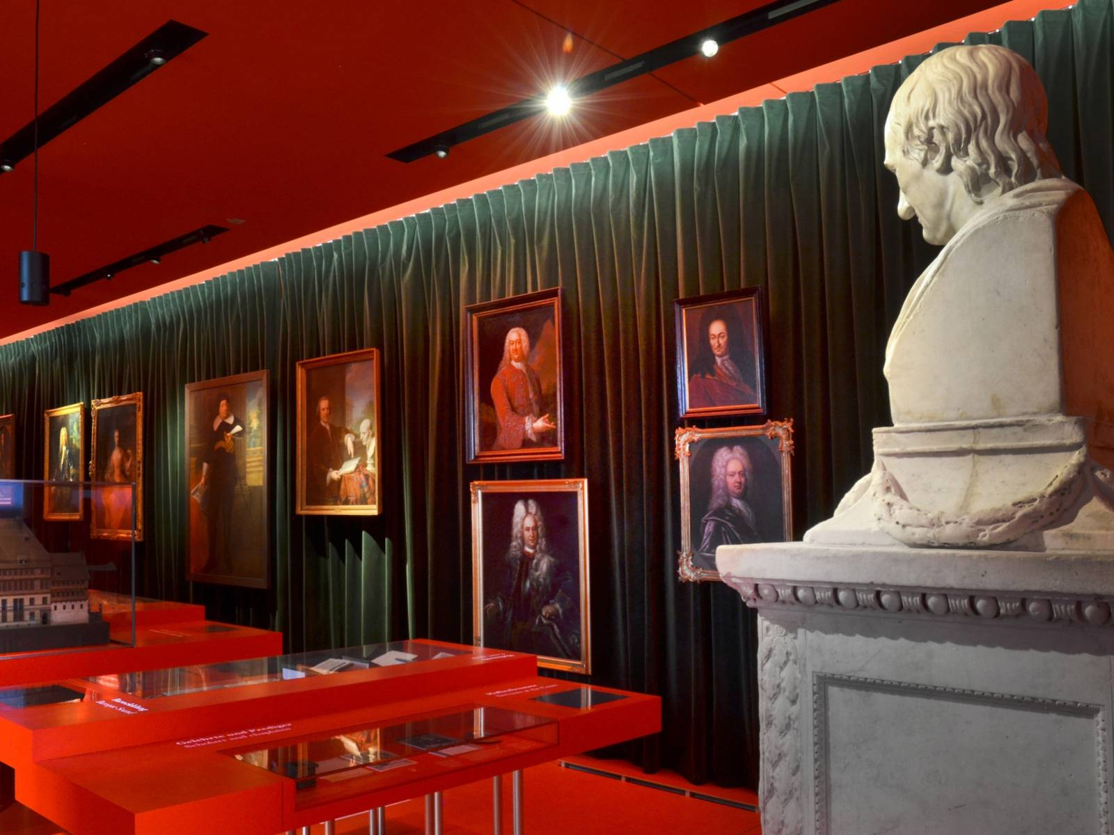 Blick in den Barockflügel des Museums Schloss Herrenhausen, im Vordergrund rechts eine Büste des Universalgelehrten Leibniz, im Hintergrund hängen diverse Portraitbilder vor einem grünen Samtvorhang
