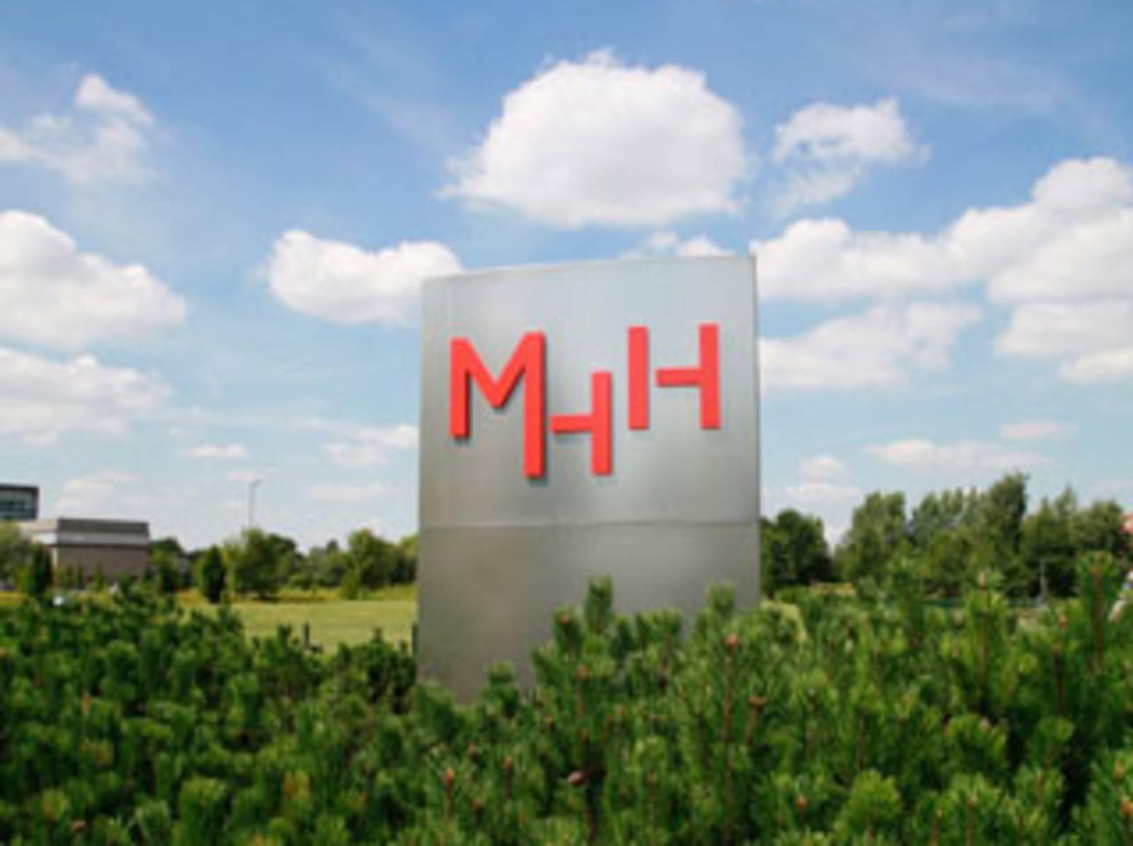 Stele mit dem Schriftzug MHH inmitten von Bäumen
