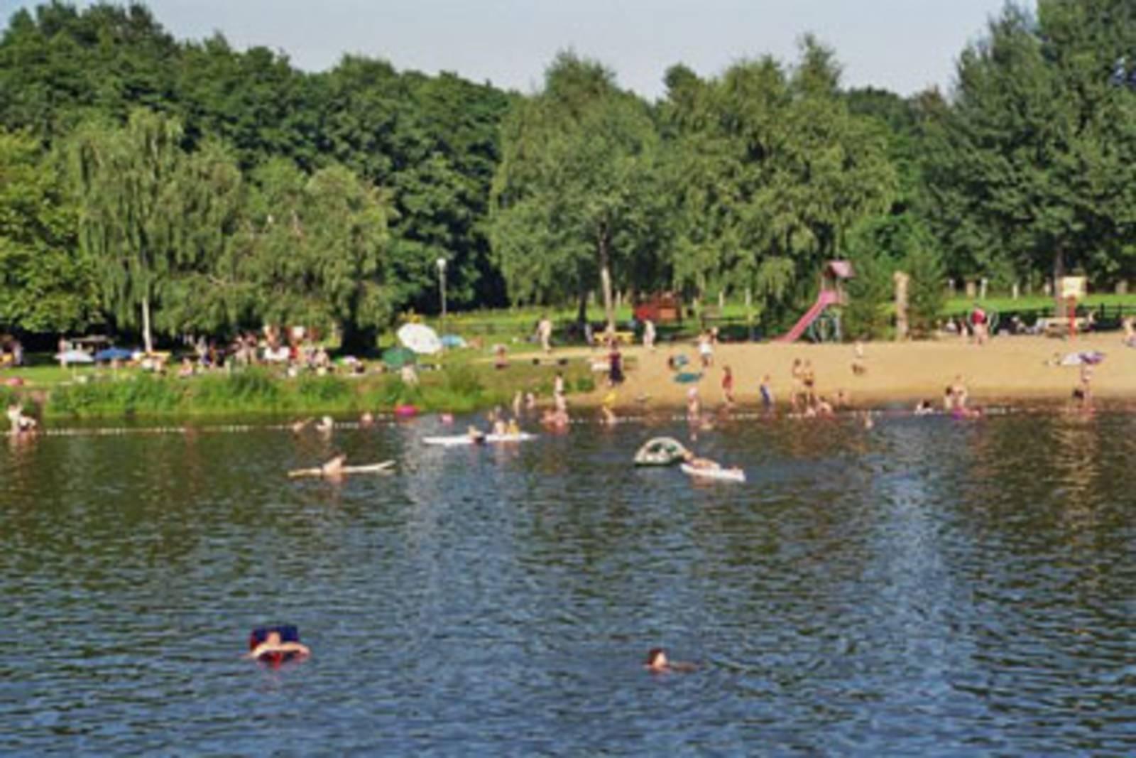 Im See schwimmende und spielende Personen, im Strandbereich Badegäste und Spielgeräte, dahinter Liegewiese und Wald