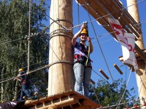 Eine Frau steht auf einer Holzplattform weit über dem Erdboden. Sie st mit Helm, Klettergeschirr und einem Seil gesichert und macht sich bereit, an einem horizontal gespannten Seil zur nächsten Plattform zu klettern.