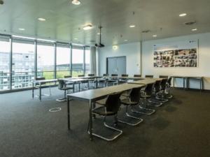 Tagungsraum mit Fensterfront. Stühle und Tische sind in U-Form aufgebaut.