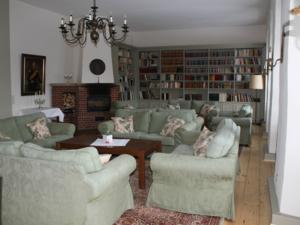 Das Kaminzimmer im Johanniterhaus. Aufgepolsterte Möbel, eine riesige Bücherregalwand und ein aus Stein gebauter Kamin.