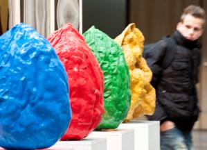 Ein junger Mann schaut sich vier bunte Objekte in Nussform an.