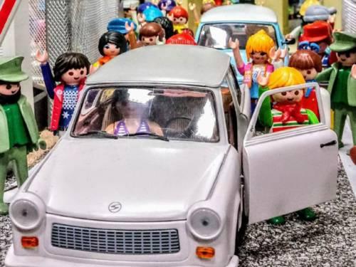 Playmobil-Figuren stehen zu beiden Seiten neben zwei Playmobil-DDR-Fahrzeugen.