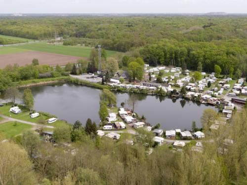 Luftaufnahme eines Natursees mit Gebäuden, Wohnwagen und Wald