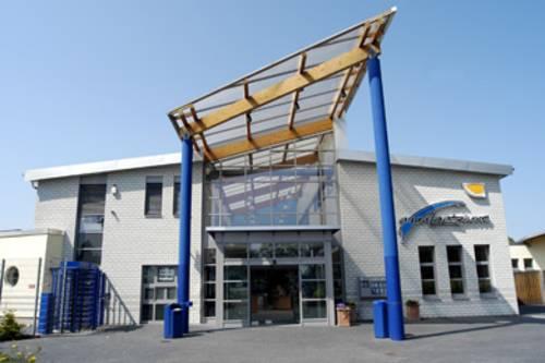 Gebäudeeingang mit einem Glasdach auf blauen Stahlsäulen