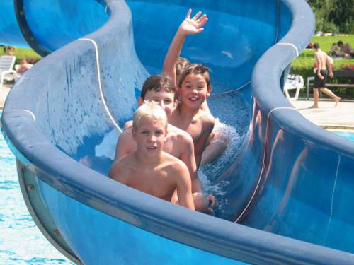 Drei Jungs auf einer kurvigen Wasserrutsche