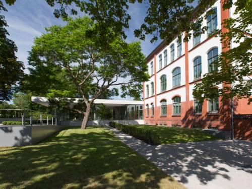 Das Gebäude der Gedenkstätte Ahlem von außen, umgeben von mehreren Bäumen.