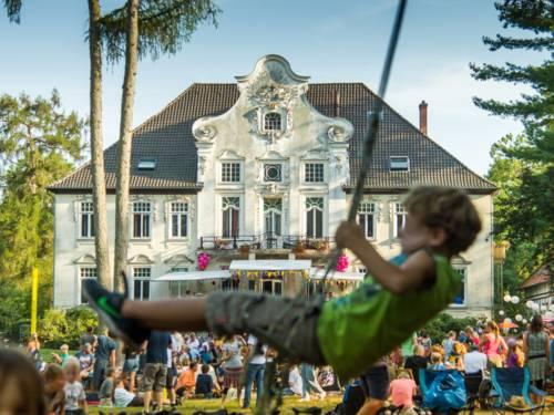Ein Junge schaukelt. Im Hintergrund ist eine Rasenfläche vor einem Haus zu sehen, auf der sich viele Menschen befinden.