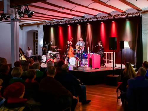 Kleine beleuchtete Bühne und davor Stuhlreihen, die mit Publikum besetzt sind.