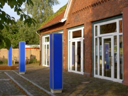 Vor einem roten Backsteinbau stehen drei blaue Säulen.