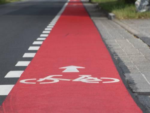 Straße mit einem rot markierten Fahrrad-Schutzstreifen
