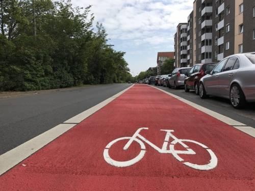 Eine Straße mit roter Markierung und einem weißen Fahrradpiktogramm