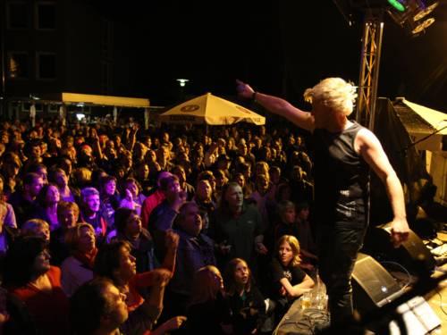 Ein Mensch auf einer Bühne, davor Publikum.