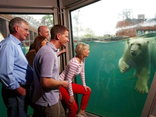 Fünf Menschen schauen in Richtung eines Wasserbeckens.