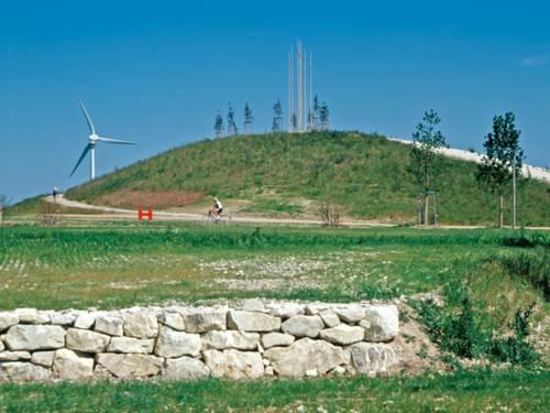 Hügel mit Fahrradfahrer, im Hintergrund ein Windrad