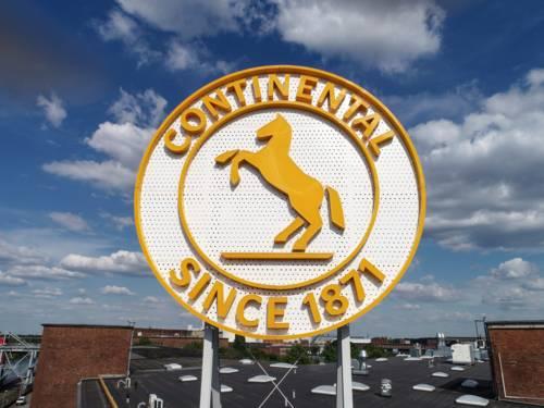Auf einem Fabrikdach trohnt ein großes rundes Logo.