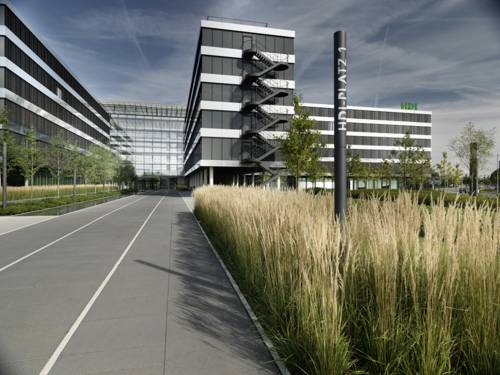 Vor einem modernen Bürogebäude sind Fahnen mit Firmenlogos gehisst.