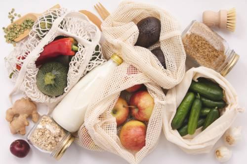Netze voller Obst und Gemüse, dazwischen eine Milchflasche. Außerdem zwei Schraubgläser mit Reis und Haferflocken.