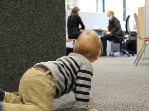 Kleines Kind krabbelt im Vordergrund, während sich die Mutter im FamilienServiceBüro beraten lässt