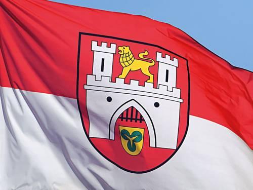 Die Hannover-Flagge mit dem Stadtwappen weht vor blauem Himmel
