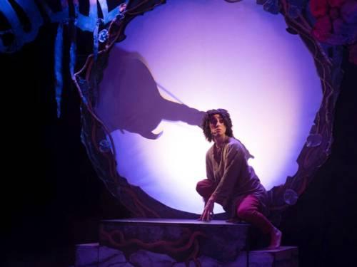Ein Schauspieler kniet vor einer Leinwand für Schattenspiele.