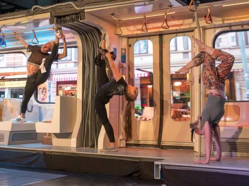 Zwei Frauen und ein Mann turnen auf einer Bühne, die dem Inneren einer U-Bahn nachempfunden ist