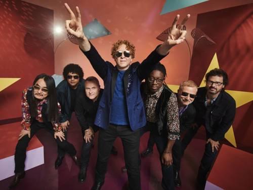 Sieben Männer, der Mann in der Mitte streckt beide Arme hoch