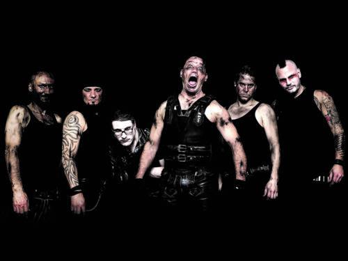 Sechs Männer mit Tattoos und schwarzer Kleidung schauen grimmig in die Kamera. Der Mann in der Mitte schreit.