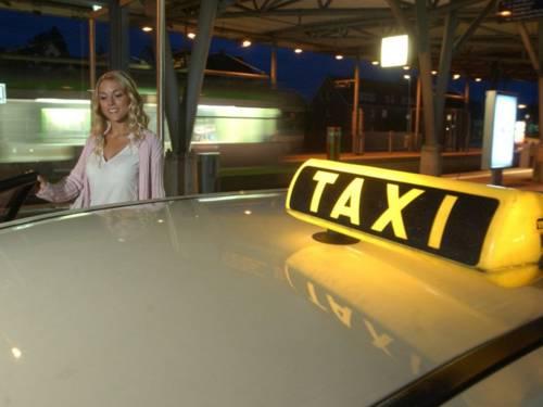 Frau, die in ein Taxi steigt.