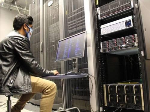Mann mit Nasen-Mundschutz-Maske sitzt in einem Rechenzentrum vor einem Bildschirm