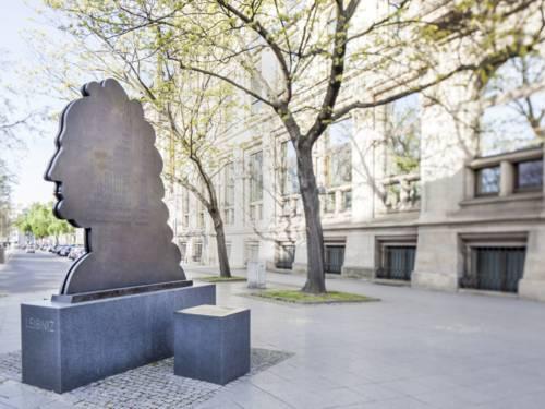 Denkmal im Form einer zwei Meter hohen, flachen Kopfsilhouette auf einem Bürgersteig vor einer Häuserfront.