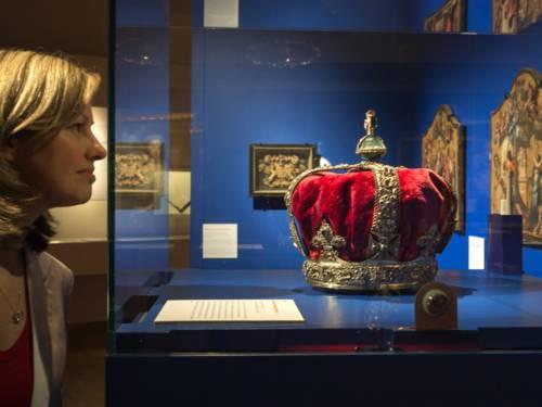 Eine Frau schaut auf eine Krone in einer Ausstellungsvitrine.