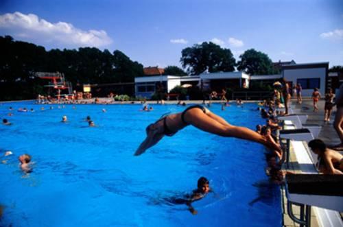 Eine Frau beim Kopfsprung vom Startblock ins Schwimmbecken, im Wasser schwimmende Menschen, im Hintergrund ein roter Sprungturm und weisse Flachdachgebäude