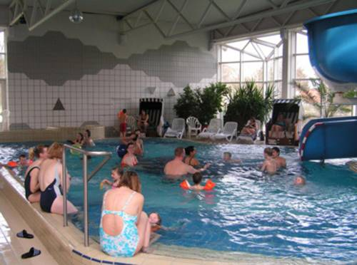 Menschen im Wasser und am Beckenrand in einem Hallenschwimmbad