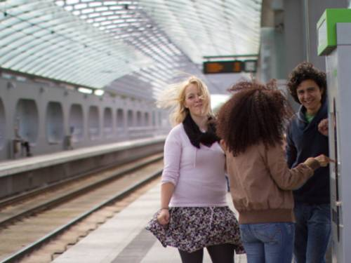 Drei Jugendliche an einer modernen Haltestelle.