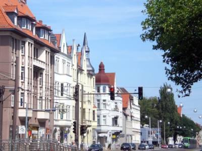 """Straßenzug an der Podbielskistraße, eine Stadtbahn """"TW 3000"""" fährt gerade eine Haltestelle an."""