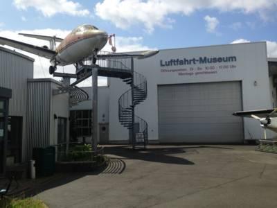 """Links ist eine Glastür, rechts eine große Halle mit einem Rolltor. Dort steht der Schriftzug """"Luftfahrt-Museum"""" und die Öffnungszeiten des Museums. Ein Flugzeug wird von Metallstreben in der Luft gehalten, eine Wendeltreppe führt zum Flugzeug."""