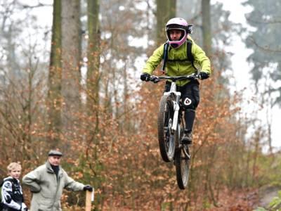 Ein Mointainbiker trägt eine hellgrüne Jacke und einen rosafarbenen Helm. Er fliegt gerade samt Fahrrad nach einem Sprung über dem Boden. Am linken Rand steht ein älterer Herr mit einem Jungen, beide schauen zu.