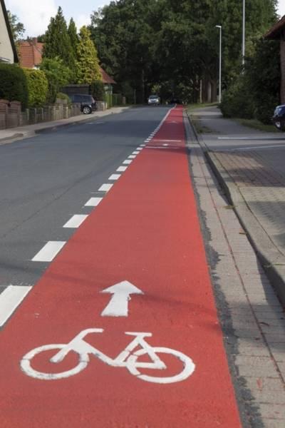 Ein roter Streifen am Rand einer Straße mit einem aufgemalten Fahrrad und einer gestrichelten weißen Linie an der Seite