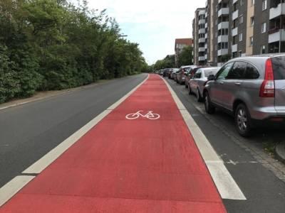 Straße mit roter Markierung und einem weißen Fahrrad-Piktogramm