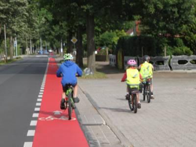 Drei Kinder auf einem Fahrrad-Schutzstreifen und Gehweg