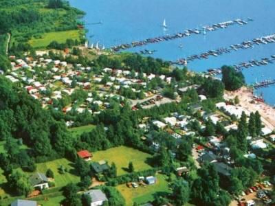 Luftbildaufnahme eines Campingplatzes mit einem angrenzenden See.