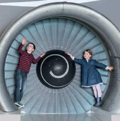 Zwei Kinder vor einer Flugzeugturbine.