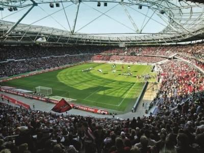 Das Bild zeigt eine Innenansicht des Hannover 96 Stadions, in dem ein Spiel ausgetragen wird.