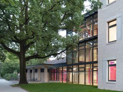 Der dreigeschossige Neubau ist an den Hauptbau des Kaiser-Wilhelm- und Ratsgymnasiums angebunden.