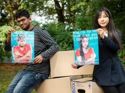 Mann und Frau halten je ein Poster
