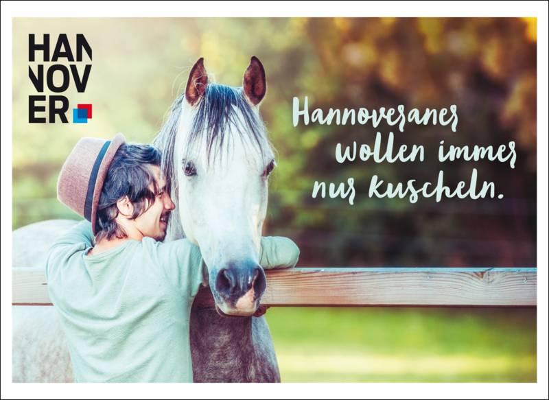 Ein Mann umarmt ein Pferd.