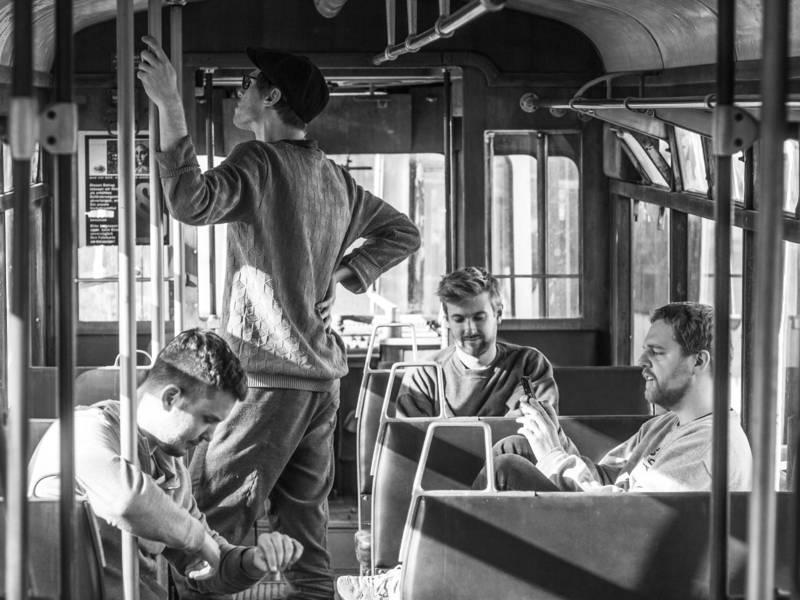 Vier Männer in einer alten Straßenbahn