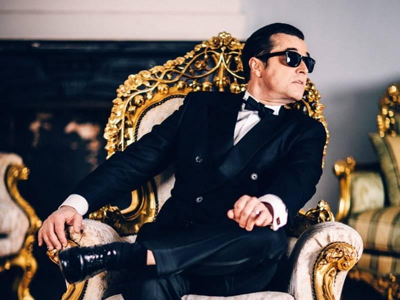 Ein Mann in einem schwarzen Anzug mit einer Sonnenbrille auf, sitzt auf einem goldenen Tron und schaut zur Seite.